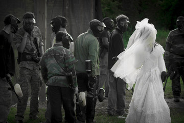bride in gown with paintball players