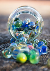 Glass jar full of crushers, fallen on the street. Front view of jar. Bright picture, with blue as main color. Front and background blurred. Other colors red, green, yellow.