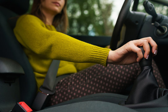 Woman shifting gears on gearbox and driving car