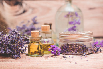 Lavender oil with fresh flowers on wooden background.