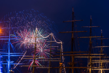 An abstract image of a spectacular firework display taken with the masts of ships in the foreground