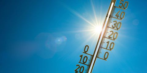 Rekordhitze, Thermometer mit strahlender Sonne und blauem Himmel im Hintergrund