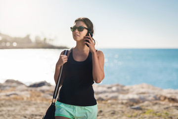 Young pretty woman on beach talking on mobile
