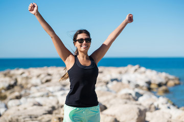 Happy young woman raising hands in victory gesture