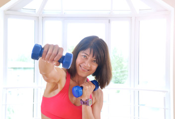 Mature woman working out with dumbbells
