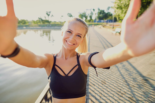 A smiling girl takes a photo  selfie on phone in the park.