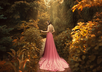 The Elf walks in the autumn garden. A girl with long ears in a beautiful pink dress with an open back and with a long train. Artistic processing Wall mural