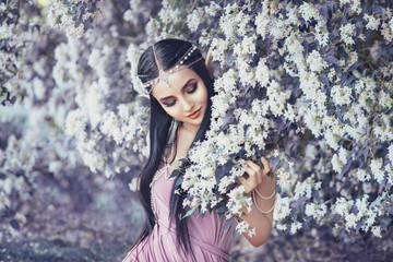 Portrait of an elf in a blooming garden. A girl with long ears touches the flowers. She is dressed in a purple dress with pearls.