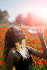 girl in field of poppy seed drink water from bottle