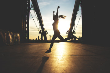 She is a winner! Silhouette of young sporty woman keeping arms raised up while jogging on bridge with evening sunset on background.