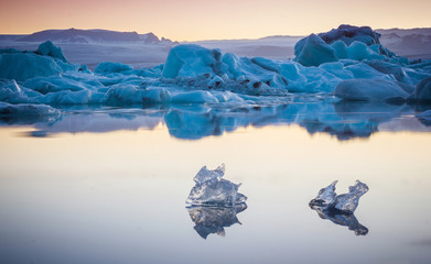Two small pieces of ice flowing and reflecting in cold lake with a big icebergs behind, jokulsarlon glacier lagoon, Iceland