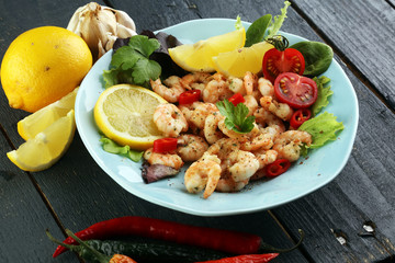 fresh shrimps served on a plate with garlic onion, lemon and chili