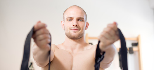 Man doing exercise with belt on a physio therapy