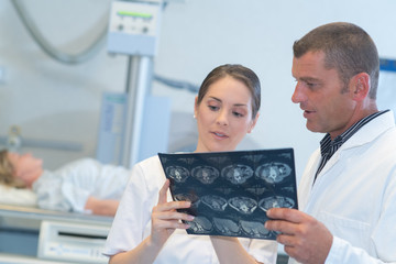 two doctors looking at x-ray with patient in the background