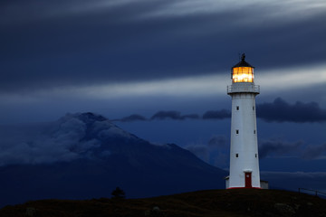 Cape Egmont lighthouse at sunset in New Zealand.