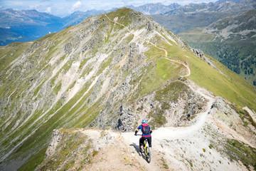 Mountain bikers on a mountain ridge line, Swiss Alps, Switzerland.