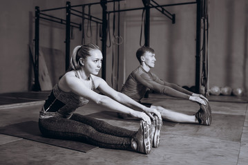 Dedicated to fitness. Side view of beautiful young woman and man doing stretching while sitting on the floor at gym.