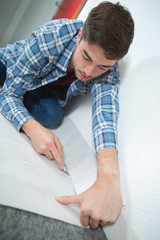 Man cutting underlay against skirting board