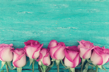 Frame of pink roses on turquoise rustic wooden background with copy space for message. Greeting card with flowers for Valentine's Day, Woman's Day and Mother's Day. Top view.