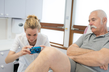 young female doctor taking photograph of senior patients leg