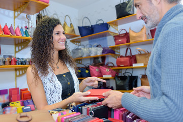 cheerful brunette girl serving male customer in wallet section