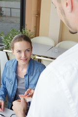attractive young brunette woman talking to waiter