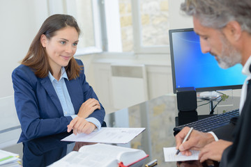 woman signing a contract with a bank director