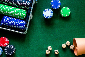 Poker set in a metallic case on a green gaming table top view copyspace