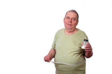 Portrait of senior elderly overweight man with measuring tape around waist and pills in hand. Age-related obesity, healthcare, diet, weight losing