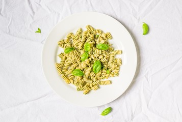 Pasta with basil and cheese pesto against white background