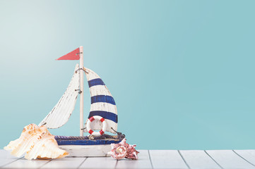 Antique sail boat Toy model with Ship'wheel, rope and seashell on white and blue wooden background - Nautical background