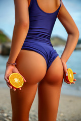 Sporty back of a beautiful woman in Swimsuit with a Orange in her hands on sea background. Sexy buttocks
