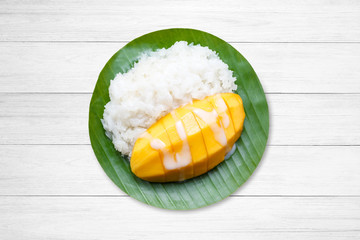 dessert sweet sticky rice with mango coconut milk on white wooden.