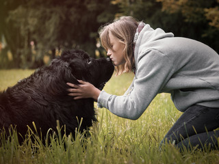 A teenage girl and a huge dog. Kiss of man and Newfoundland. Nature Park