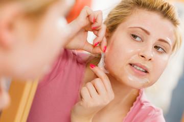 Woman peeling off gel mask from face
