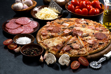 pizza with salami and ingredients on a black background