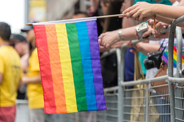 GayPride spectators carrying Rainbow gay flags during Toronto Pride Parade in 2017