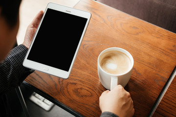 top view. business man holding tablet for checking stock graph. have coffee cup with coffee putting on table front of him. image for beverage,technology,mobile,body part concept