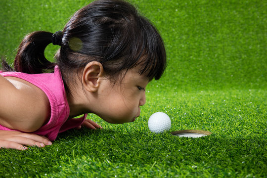 Asian Chinese little girl blowing the ball into a hole