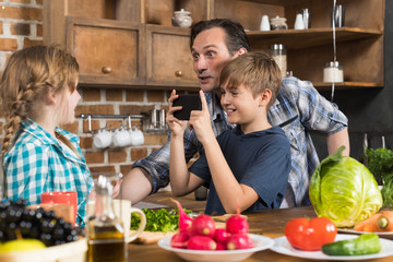 Happy Family In Kitchen, Father And Son Taking Photo Of Daughter Cooking Food On Cell Smart Phone Preparing Healthy Meal