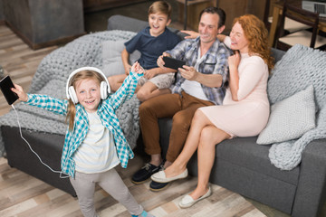 Father Taking Photo Of Daughter Listening Music In Headphones, Happy Smiling Family Sitting On Couch, Parents Spending Time With Children In Living Room