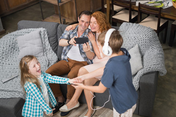 Father Taking Photo Of Daughter And Son Listening Dancing Music In Headphones, Happy Smiling Family Sitting On Couch, Parents Spending Time With Children In Living Room