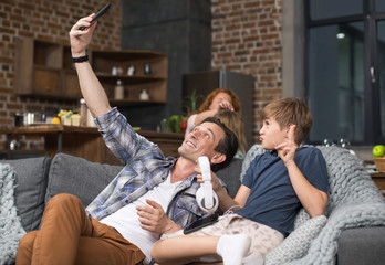Father And Son Take Selfie Photo On Cell Smart Phone Sitting On Couch, Parent Spending Time With Child In Living Room