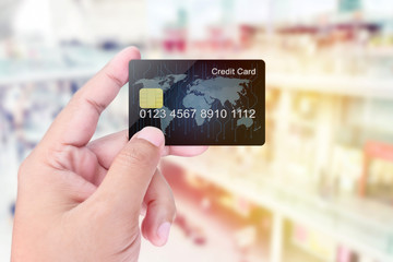 Credit Card holded by hand on blurred abstract background