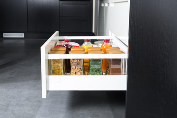 Side view of a spices and groceries organized in a modern kitchen drawer. Kitchen design inspiration.