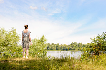 A woman standing up close to the Dnieper river in Kiev, Ukraine, observes in the distance from a raised point of view, under a soft cloudy summer sky