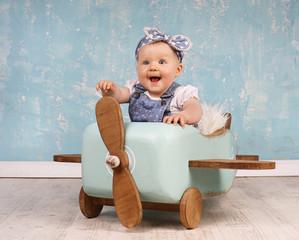 lachendes niedliches Mädchen spielt im Holzflieger