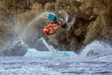 Man makes an extreme jump on wakeboarding, around there are a lot of splashes and splashes of water. This is an extreme sport. Wall mural