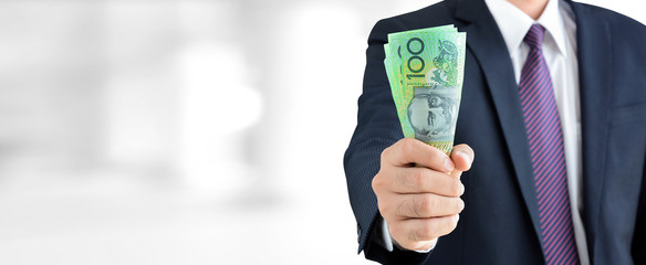 Businessman holding money, Australian dollar (AUD) banknotes, in his fist