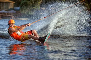 Man glides on the board on the lake. He quickly rushes creating splashes and splashes of water. Wall mural
